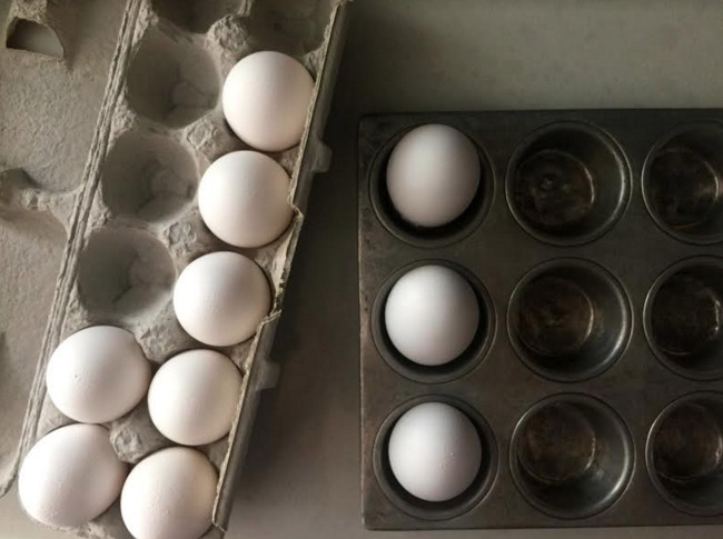carton of eggs and a muffin tin with 3 eggs in the muffin spaces