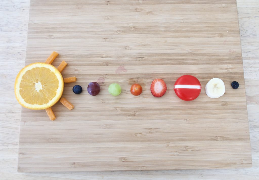 various fruits and veggies representing the solar system on a cutting board