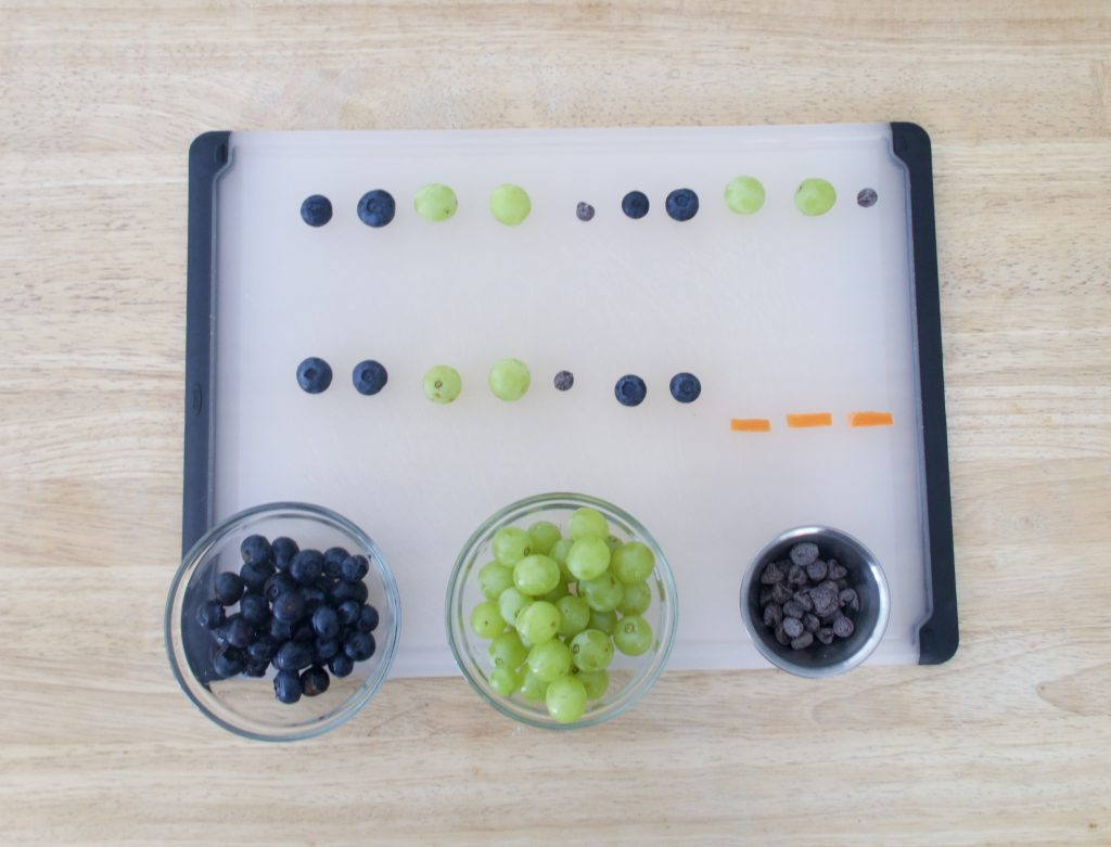 green grapes and blueberries on cutting board following a pattern