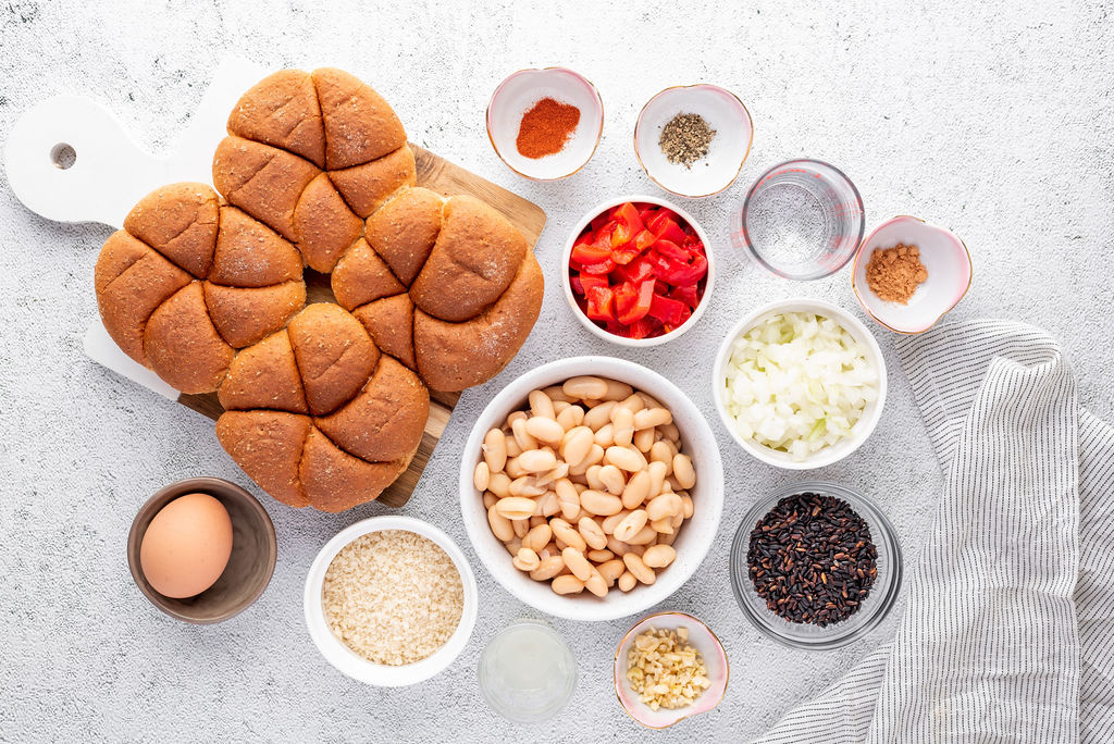 small bowls with various ingredients for bean burger recipe and a plate of buns