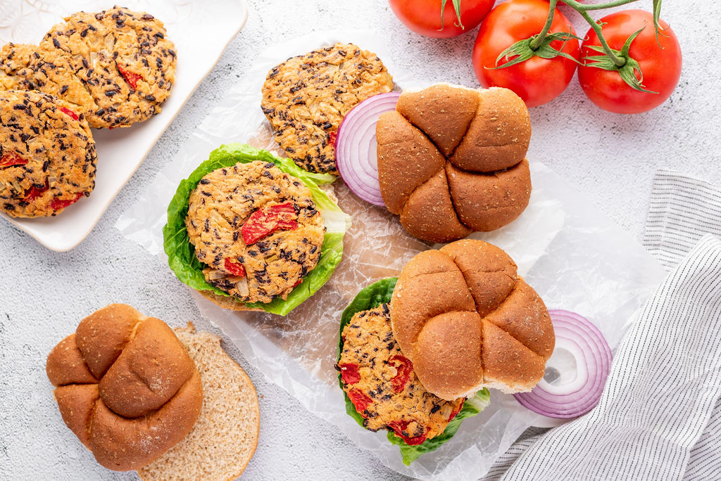 6 bean burger patties on buns and on plates with toppings and tomatoes on the vine
