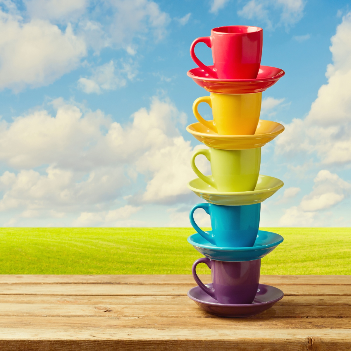 Rainbow color cups on wooden table over beautiful sky and meadow.