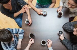 People sitting around table drinking coffee in cafe