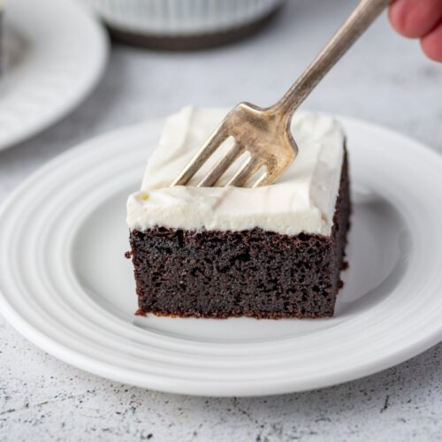 Piece of keto chocolate cake served on a plate with fork in it