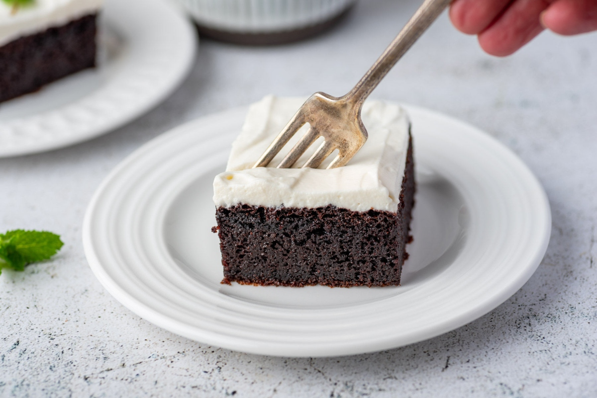 Piece of keto chocolate cake served on a plate with fork in the cake
