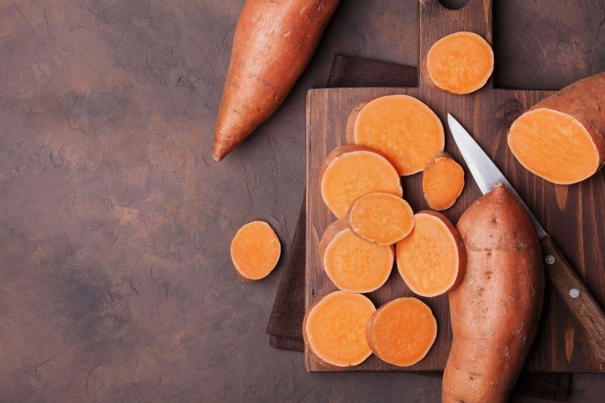 Raw sweet potatoes on a cutting board