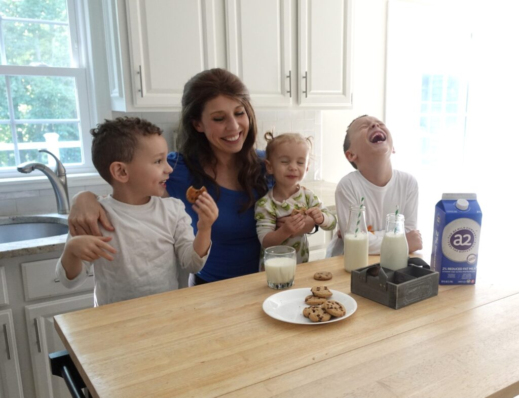mom with three young children eating milk and cookies while laughing in kitchen