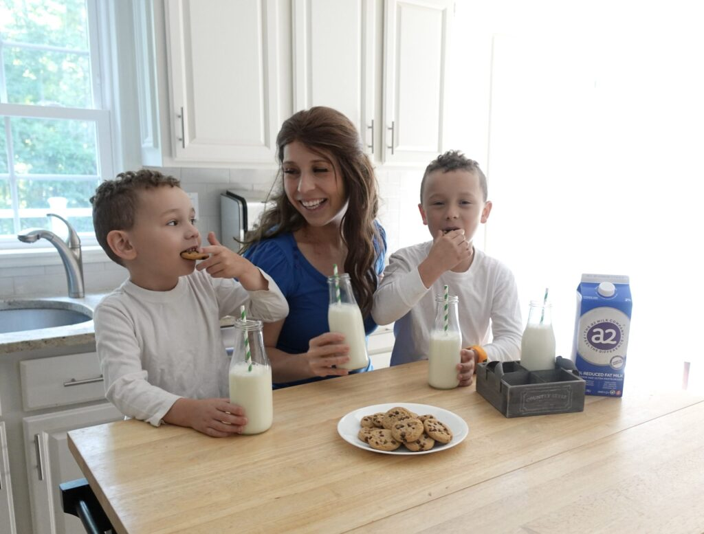 mother and sons enjoying a glass of milk and cookies while laughing