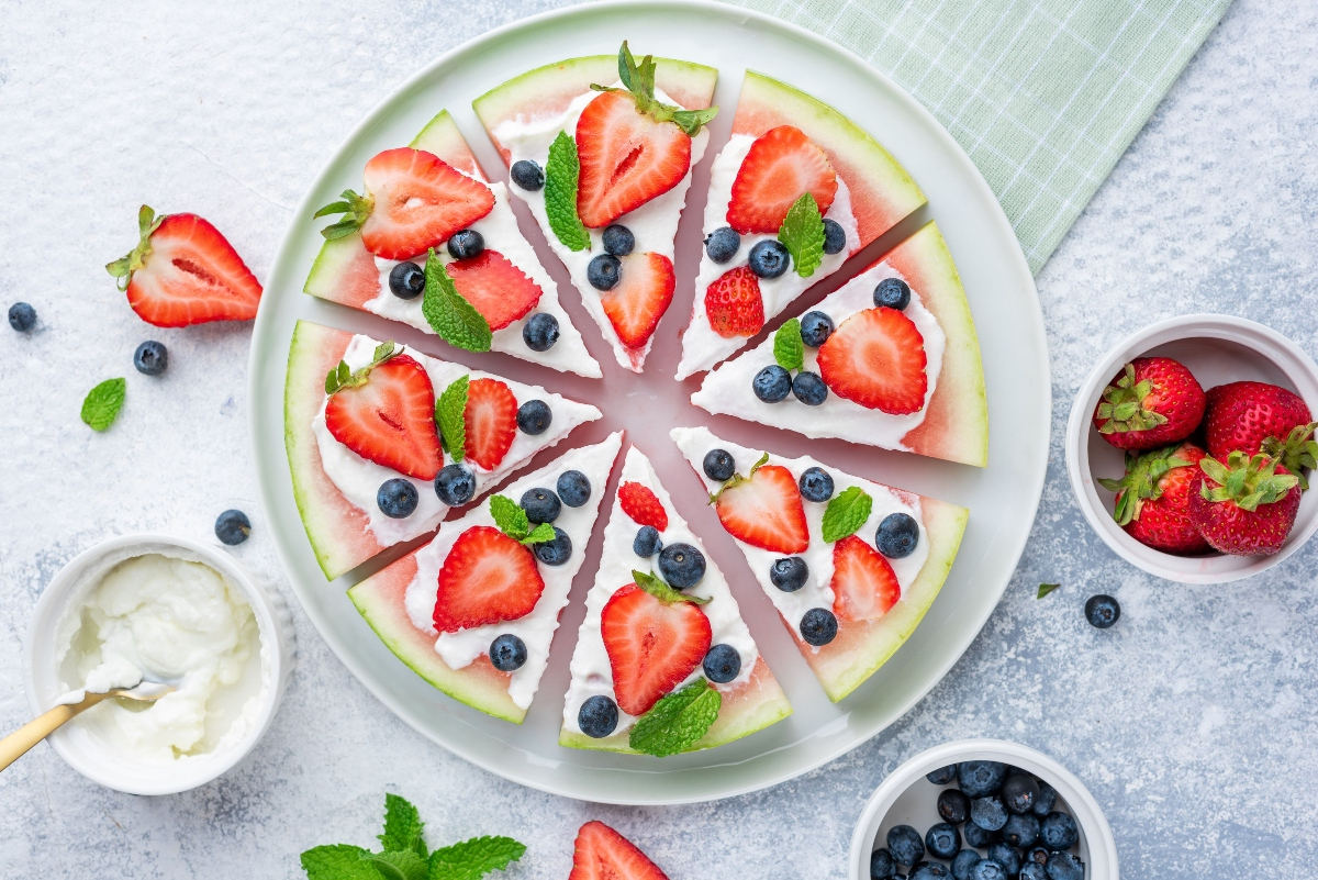 Watermelon pizza served on a plate with strawberries, Greek yogurt and blueberries in the cups around the plate