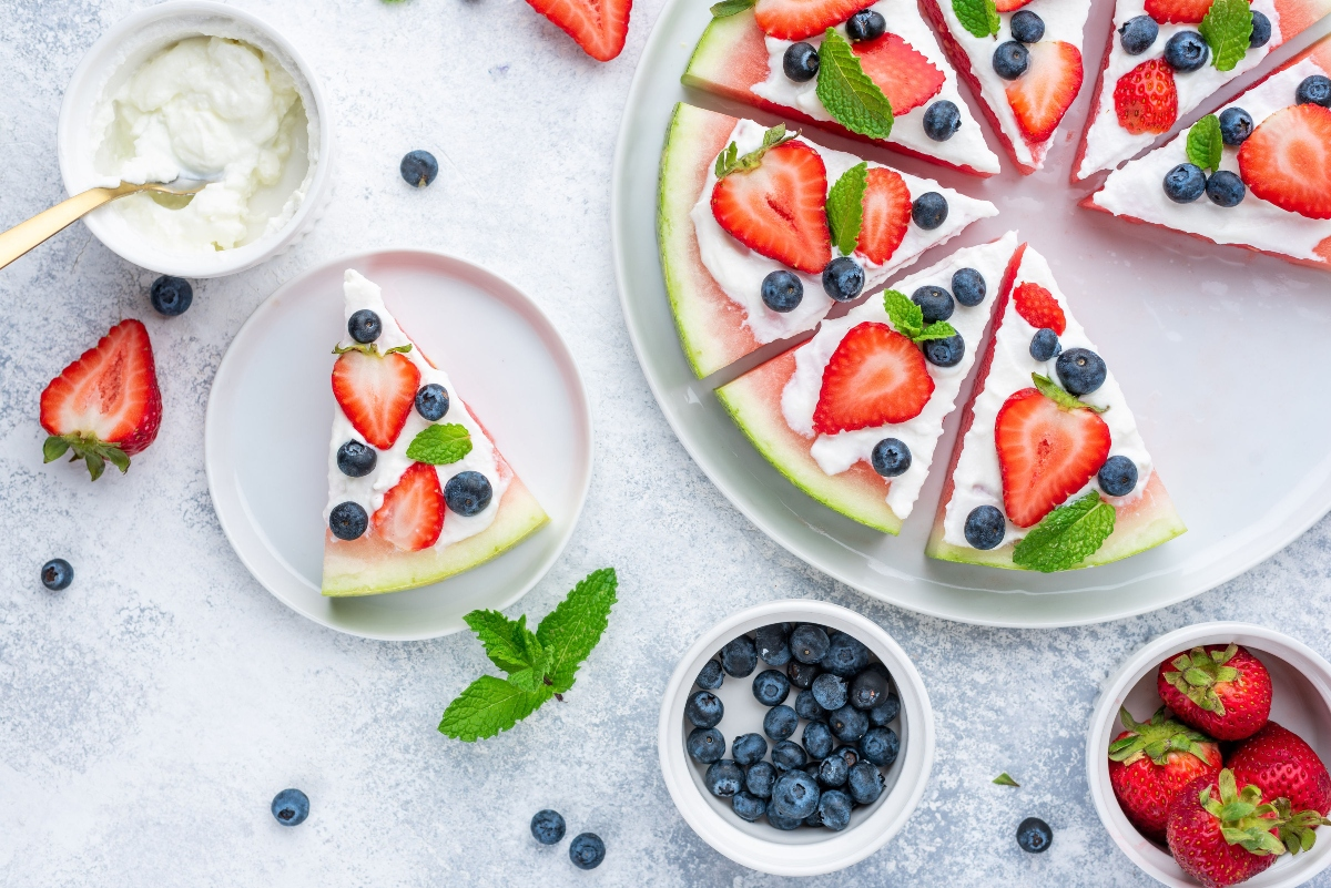 Watermelon pizza with yogurt frosting and served slice on a plate and ingredients in the cups around the pizza