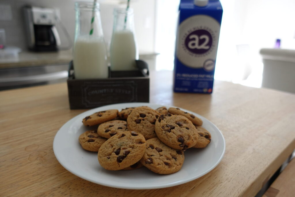 white plate filled with chocolate chip cookies with glass jars of milk and carton in background