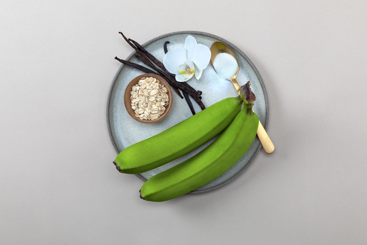 white plate with orchid, green bananas, and rolled oats