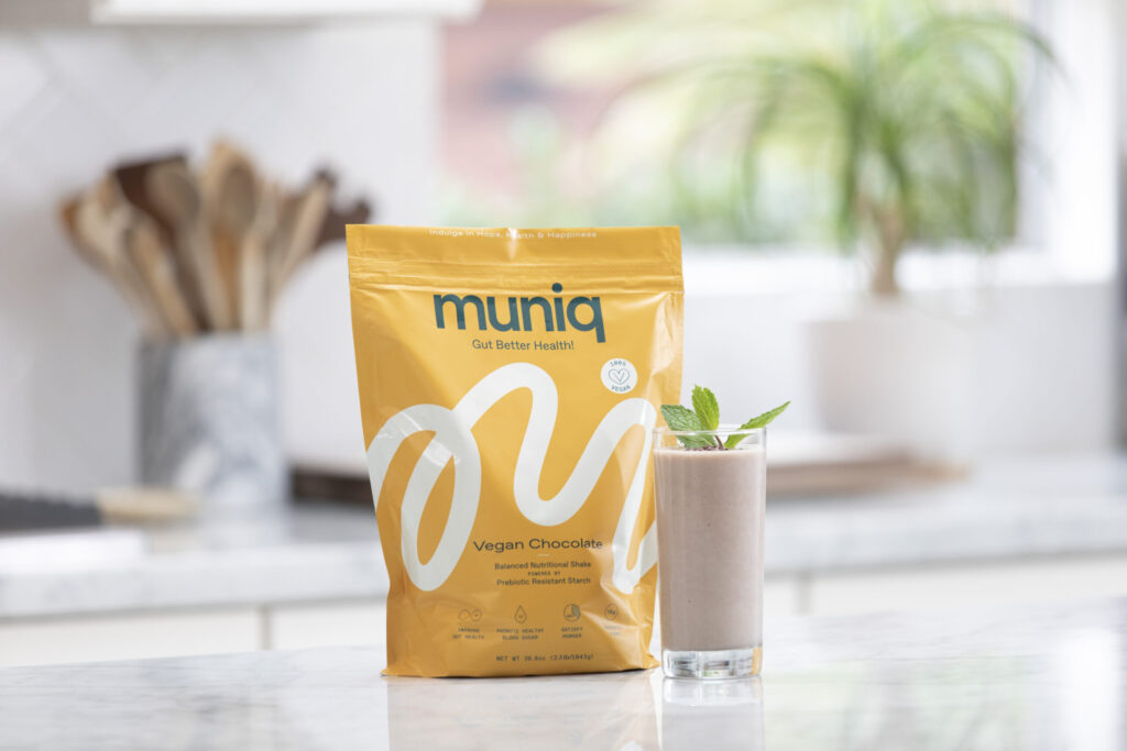 bag of muniq shakes with prepared chocolate shake in clear glass