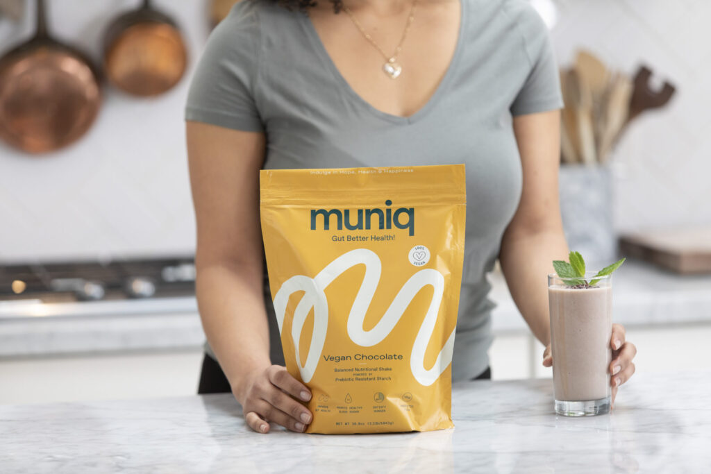 woman's hand on bag of Muniq shakes next to chocolate smoothie in glass