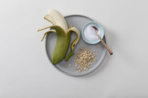 partially peeled banana, yogurt with spoon, and oat flakes on circular plate