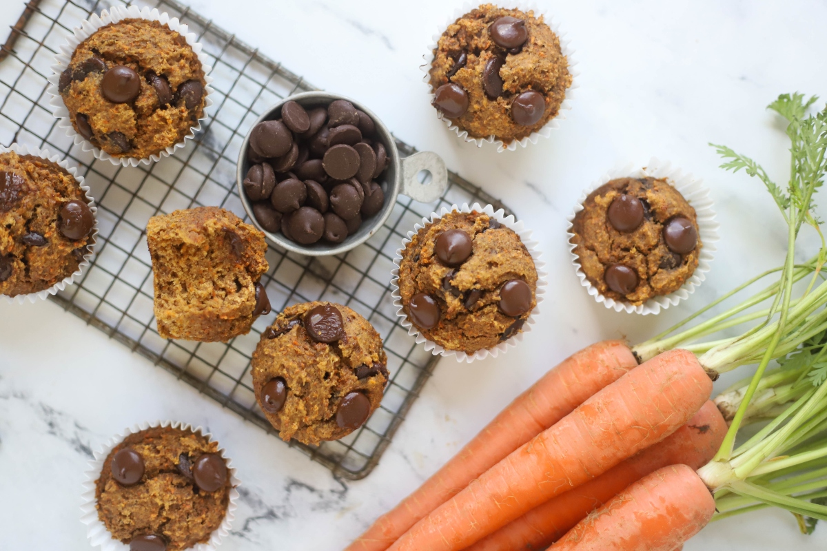 Banana Carrot muffins with dark chocolate chips in the cup beside and bunch of carrots