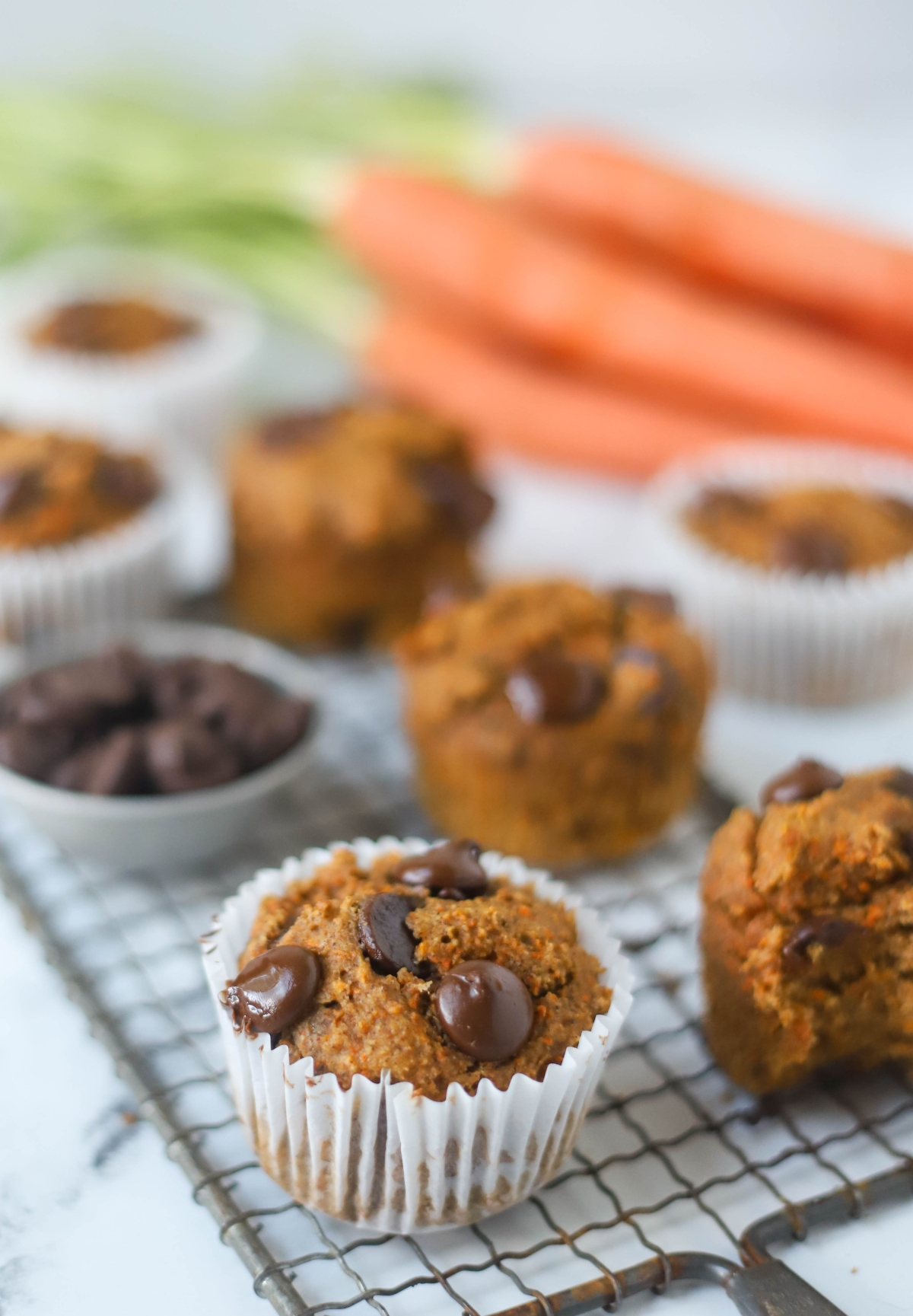 Banana Carrot Muffin closeup with other muffins and a cup of dark chocolate chips blurred behind
