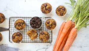 Banana Carrot Muffins with chocolate chips in a bowl and carrots beside them