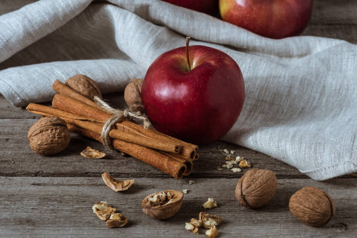 Red apple with cinnamons sticks beside and walnuts with and without shell sprinkled around, with a white cloth in the background on wooden surface