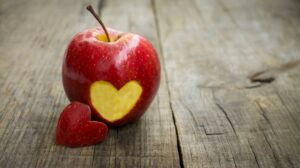 Red apple with one heart-shaped piece on wooden surface