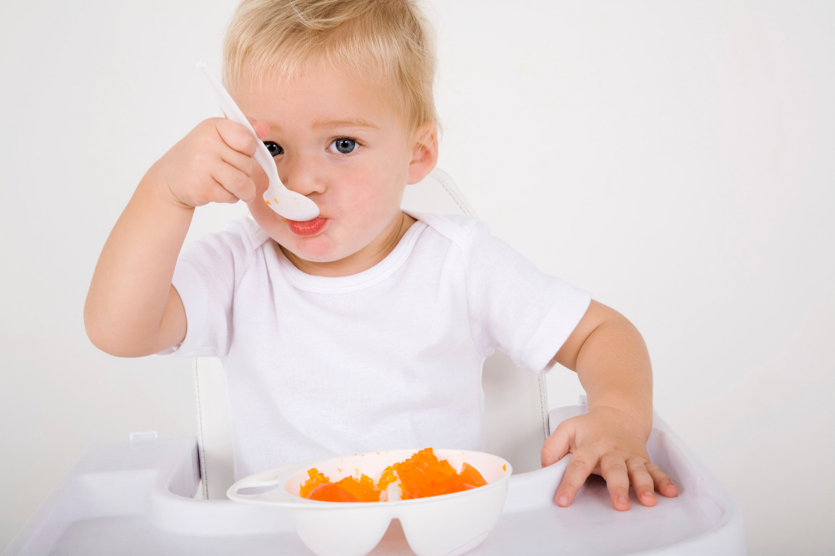 Baby eating muskmelon from the plate with a white plastic spoon