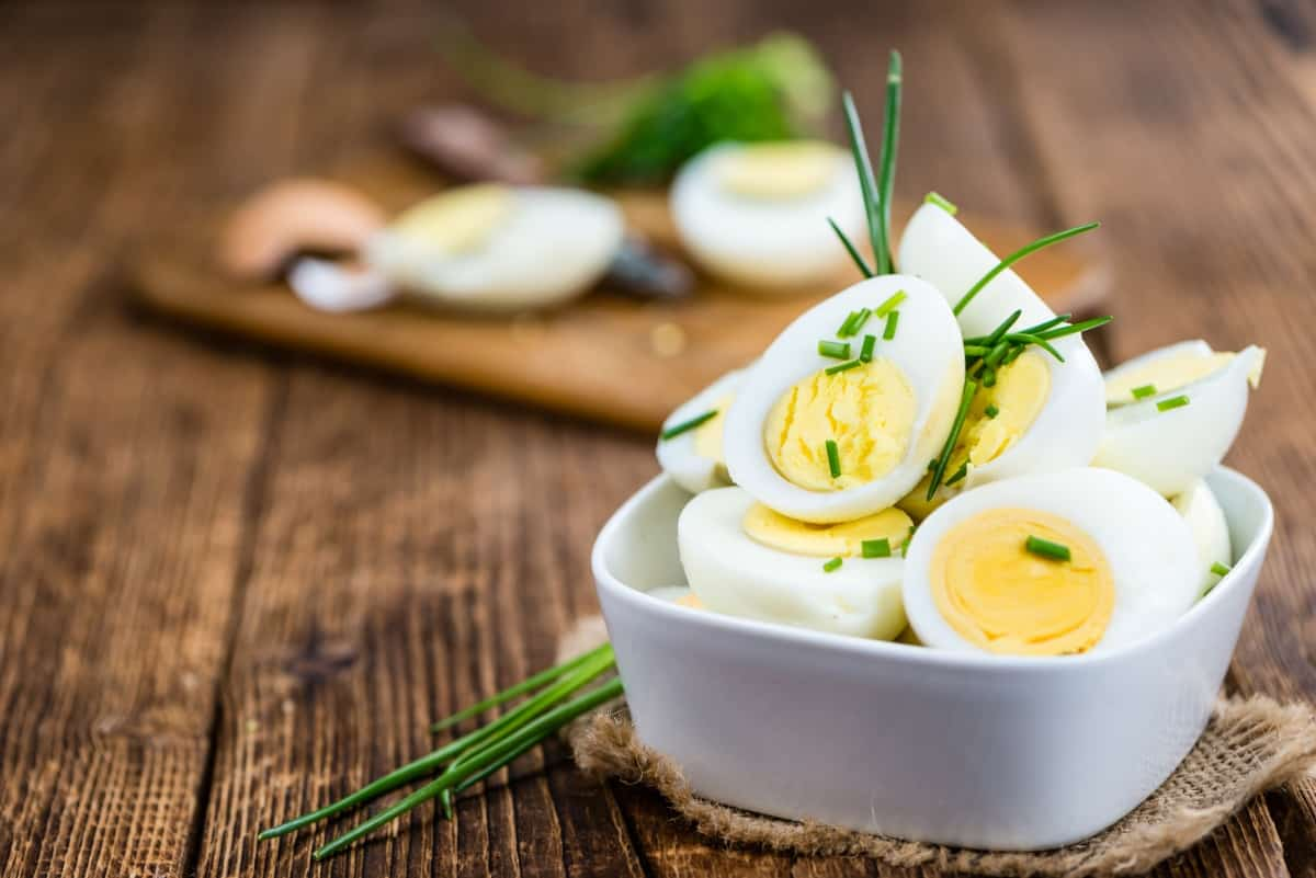 Boiled eggs cut in half in the cup with cutting board, knife and egg blurred in the background