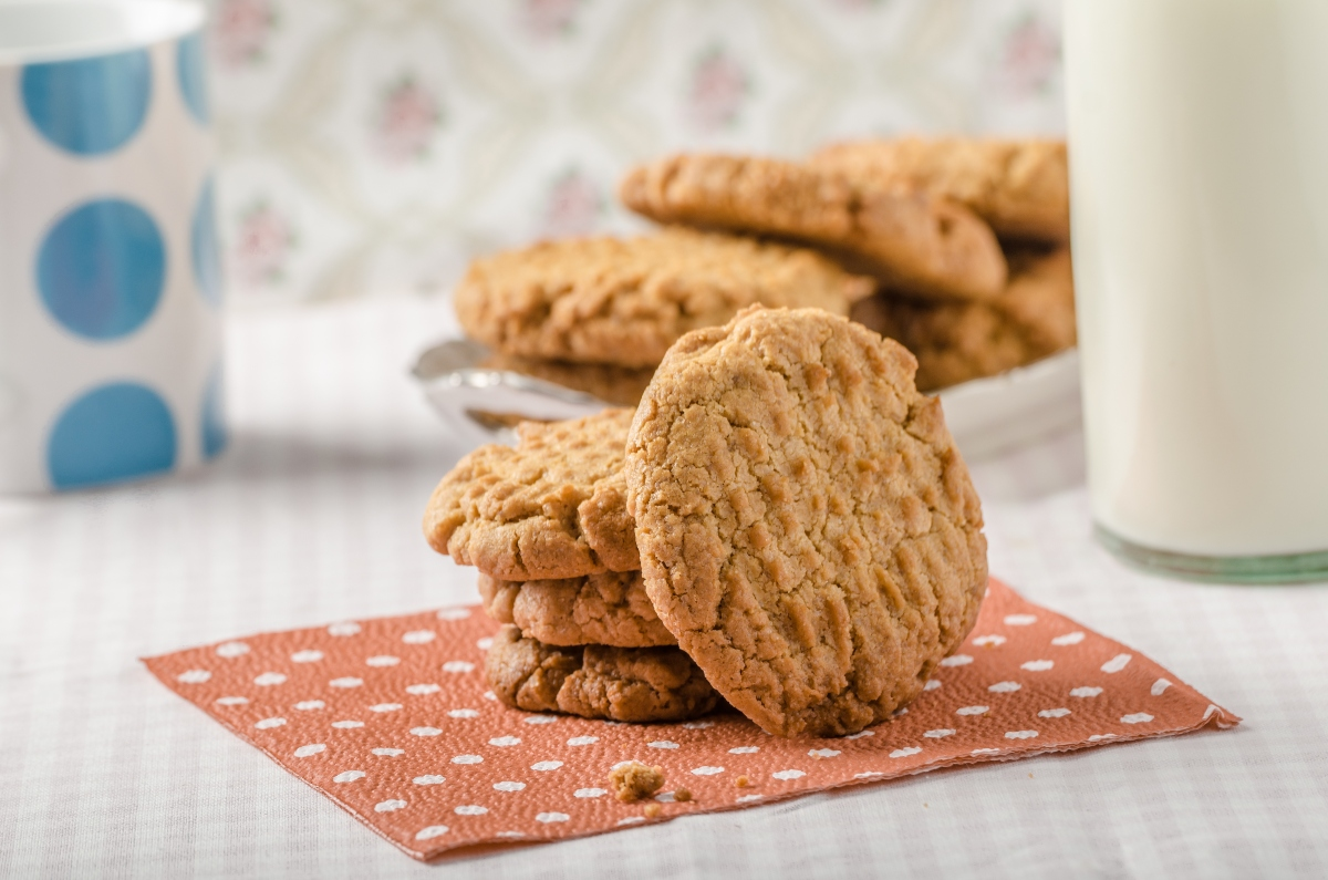 Cookies stacked on each other on dotted paper napkin with plate full of cookies and a glass of milk behind