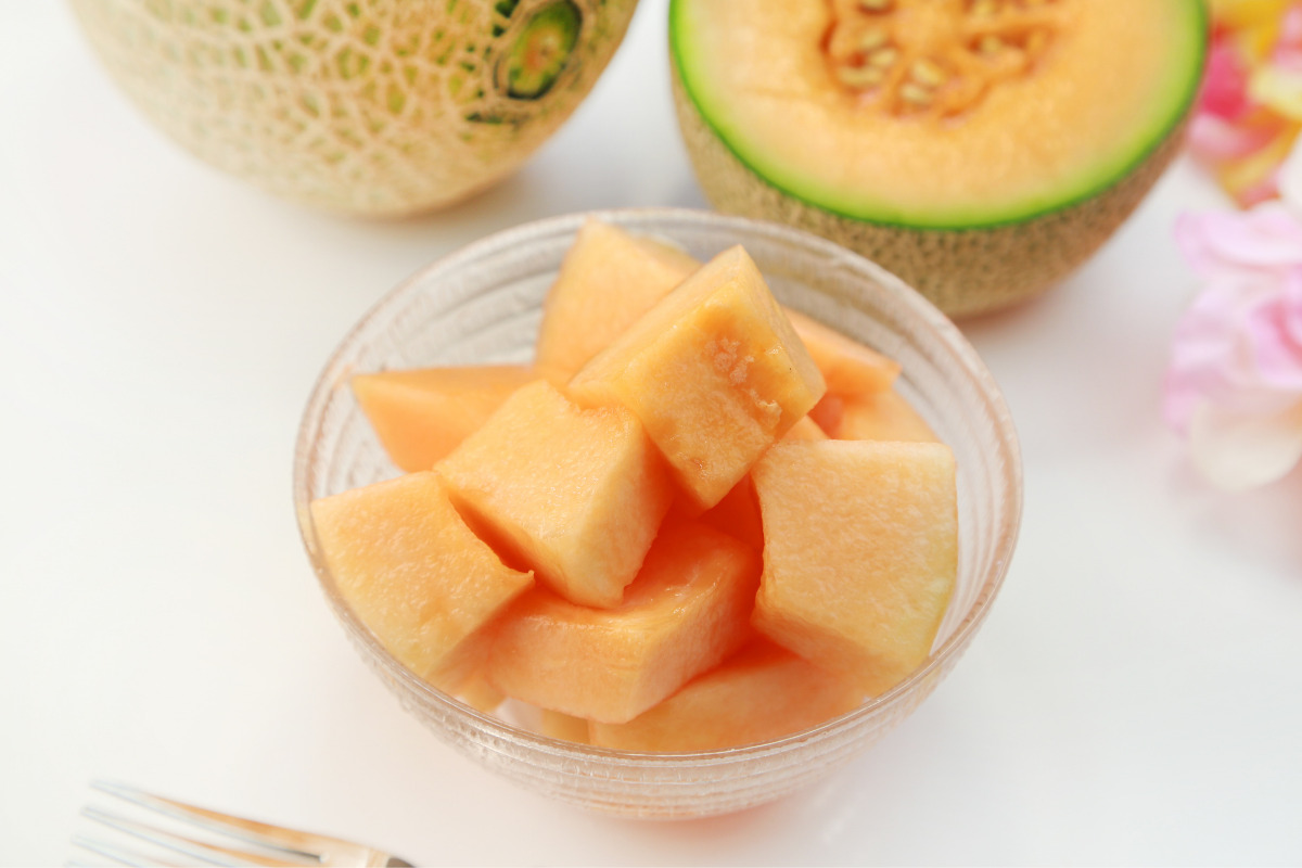 Muskmelon cut into the cubes in the cup with muskmelon cut in half behind