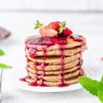 Peanut butter jelly pancakes stacked together with a couple of sliced strawberries on top, served on a white plate and glass cup with jelly and fresh mint leaves on the other side of the plate
