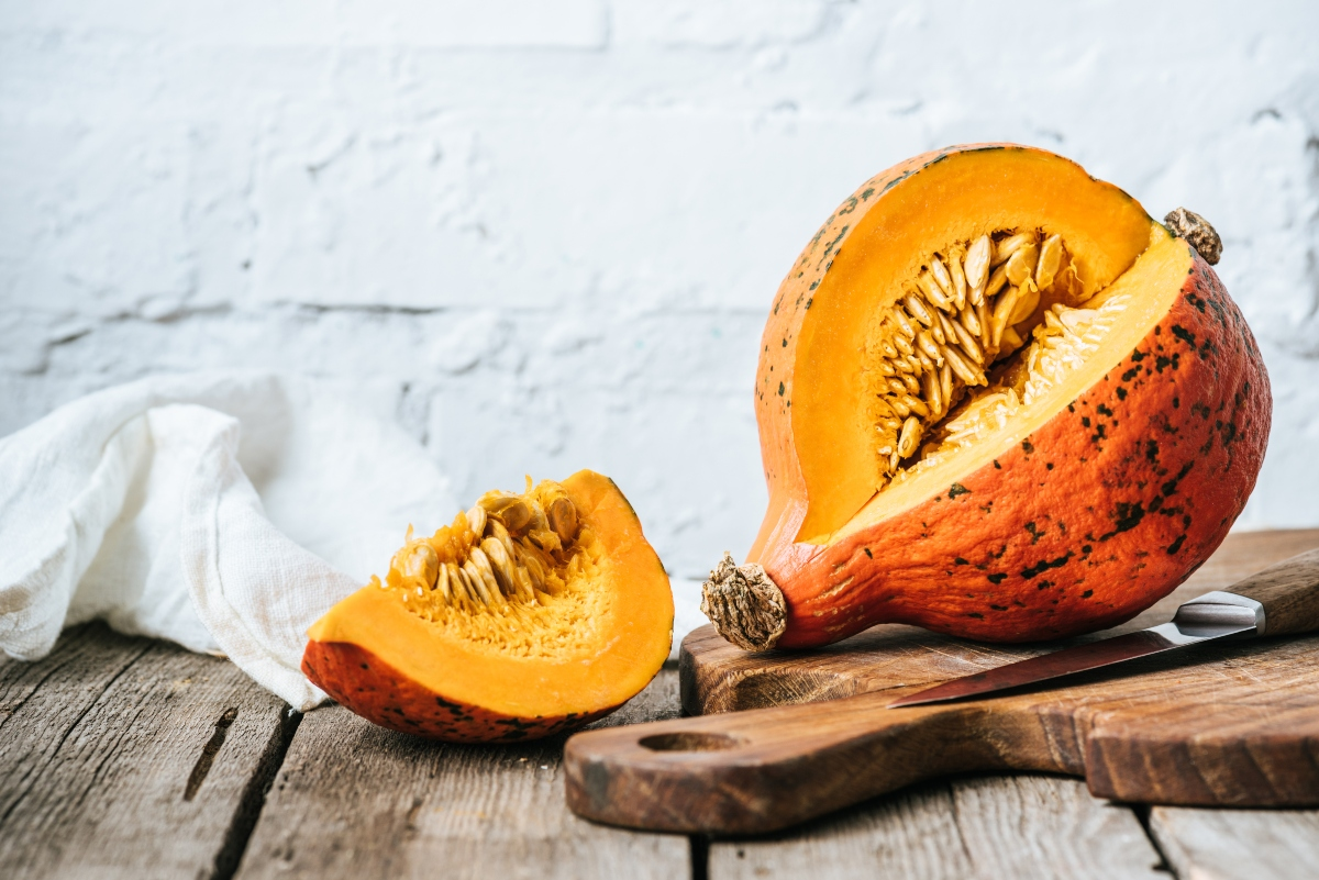 Pumpkin and its slice on cutting board
