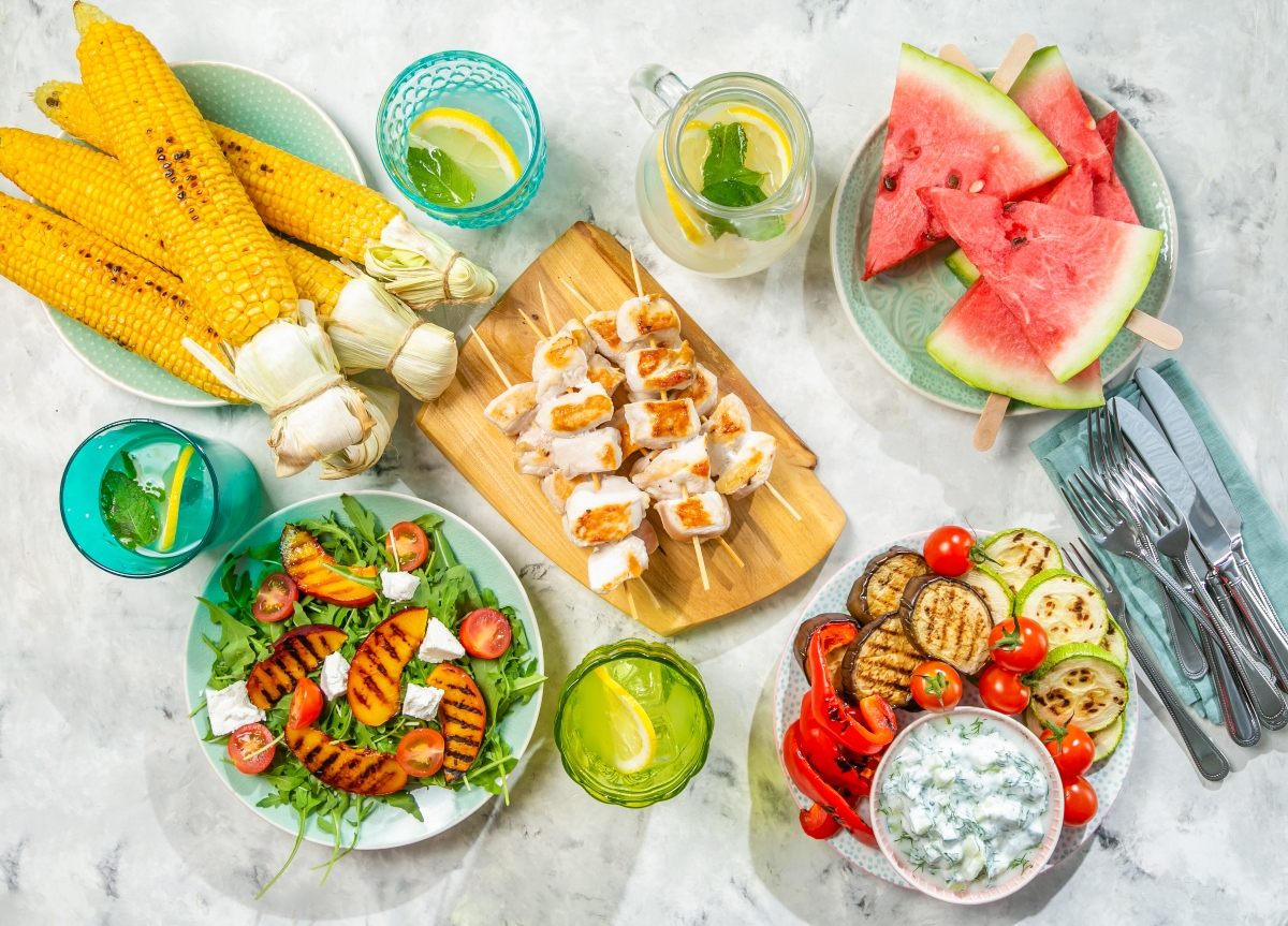 Whole foods on the table, corn cobs, watermelon, grilled vegetables, fruit and cheese salad, chicken on cutting board and glasses of lemonade