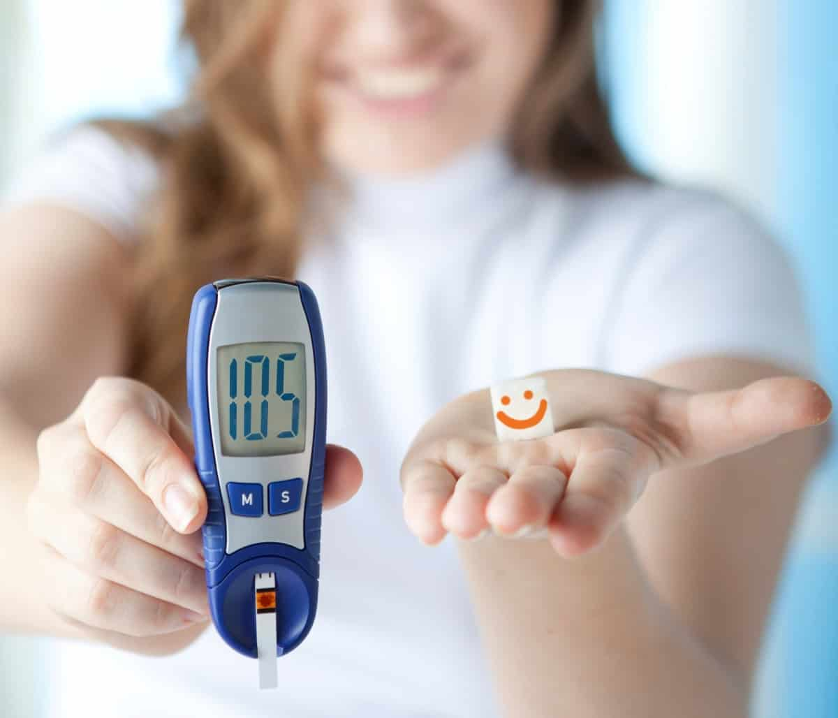 Woman holding glucometer in one hand and paper with smiley in other hand