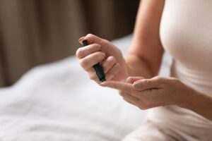 Woman measuring blood sugar level with glucometer