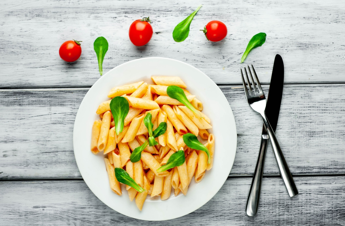 High fiber pasta in a plate with fork and knife beside and cherry tomatoes and basil leaves sprinkled beside the plate