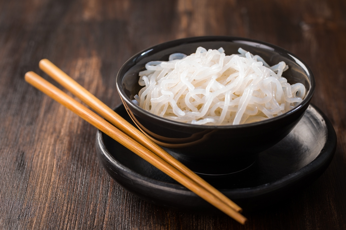 Shirataki noodles in black bowl with wooden chopsticks beside