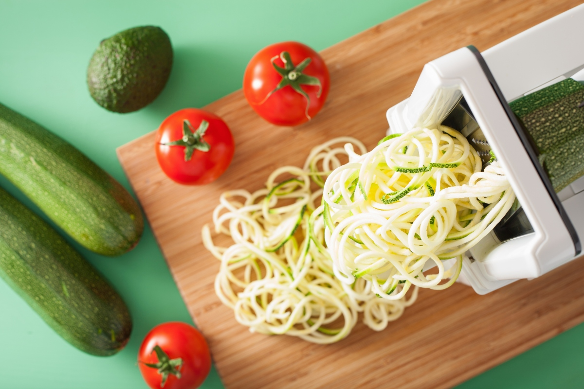 Spiralized veggie noodles on cutting board with tomatoes and zucchinis beside