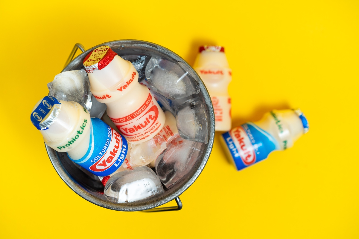 Yakult bottles in a bucket with against the yellow background