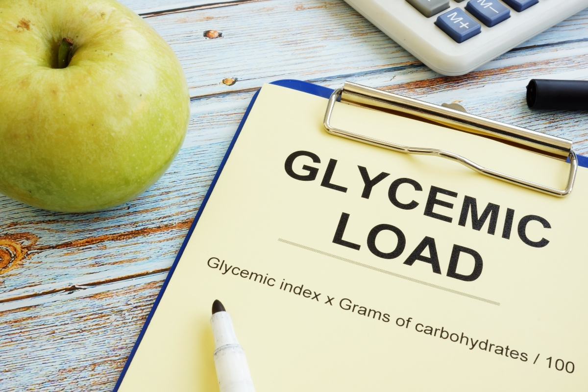 Notes with calculation formula for glycemic load with an marker on the notes and an apple and calculator beside