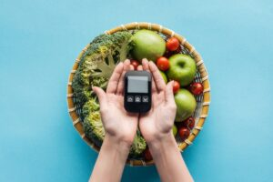 A person holding a glucometer in hands over the bowl filled with vegetables and fruits against the blue background