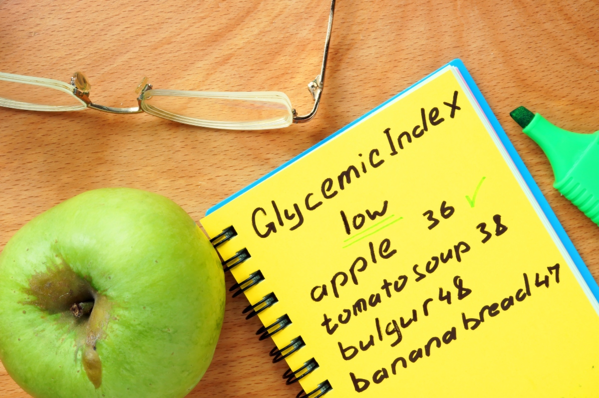 A notebook with Glycemic index calculations and a green apple and a pair of glasses beside
