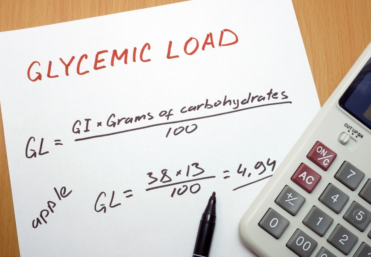 Glycemic load calculation on a paper with a pen and a calculator beside