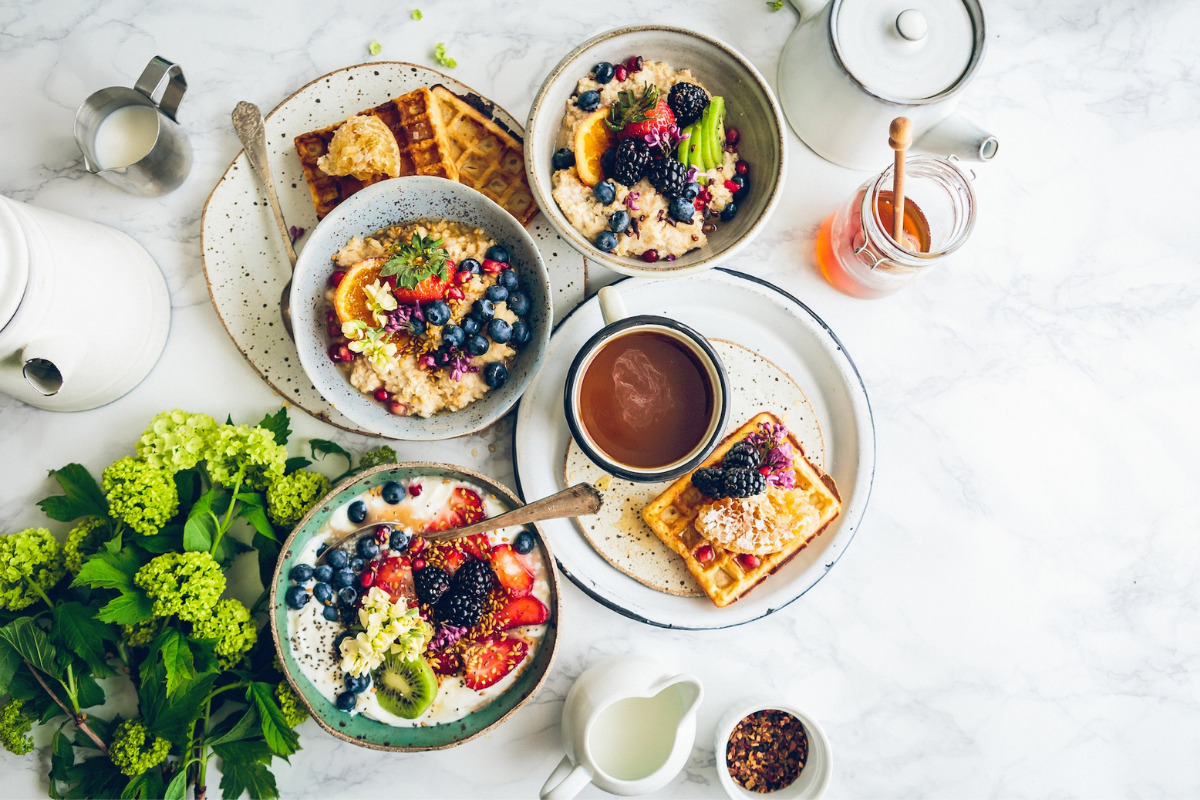 Various healthy foods on a table, waffle with fruit, salad, oatmeal and honey