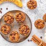 Low carb pumpkin muffins served on a plate with cinnamon stick and bananas around